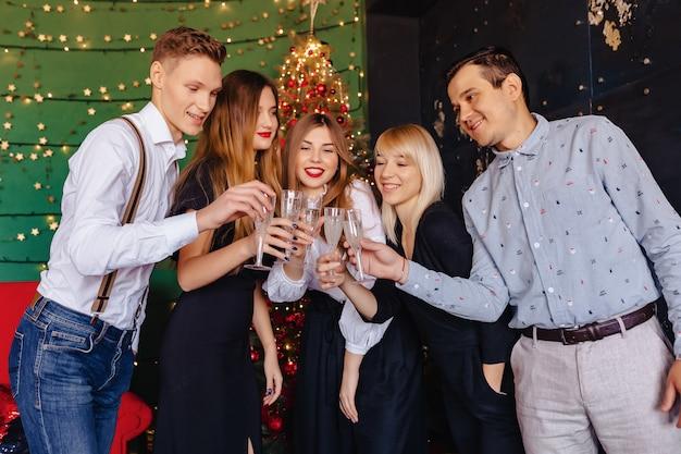 Большая компания празднует новый год с бокалами шампанского Premium Фотографии