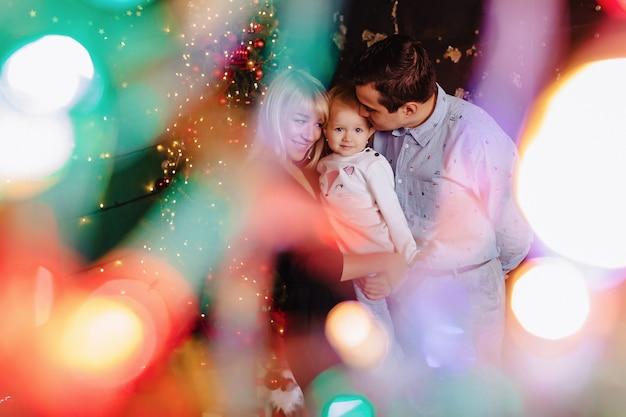 新年を祝う、クリスマスツリーの背景に小さな赤ちゃんと一緒に素敵な家族 Premium写真