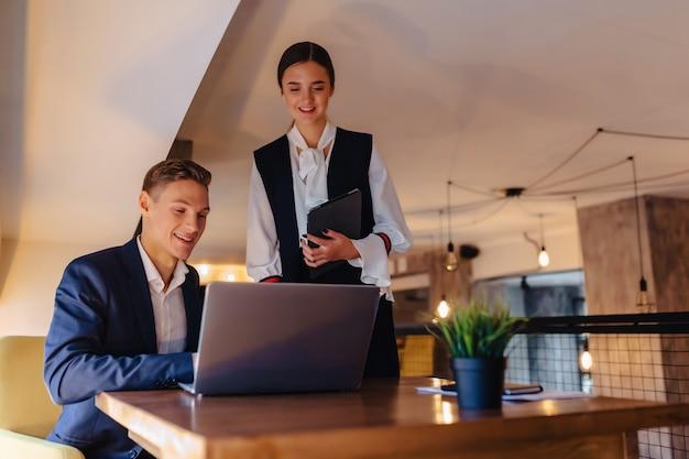 若いビジネスマンの男の子と女の子がノートパソコン、タブレット、カフェでメモを扱う Premium写真