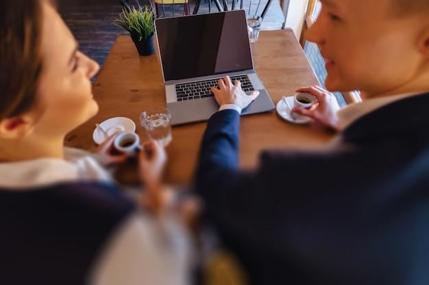スタイリッシュなカップルはカフェで朝のコーヒーを飲み、ラップトップで動作します Premium写真