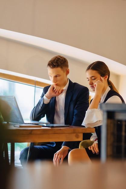 若いビジネスマンの男の子と女の子はラップトップで動作します Premium写真
