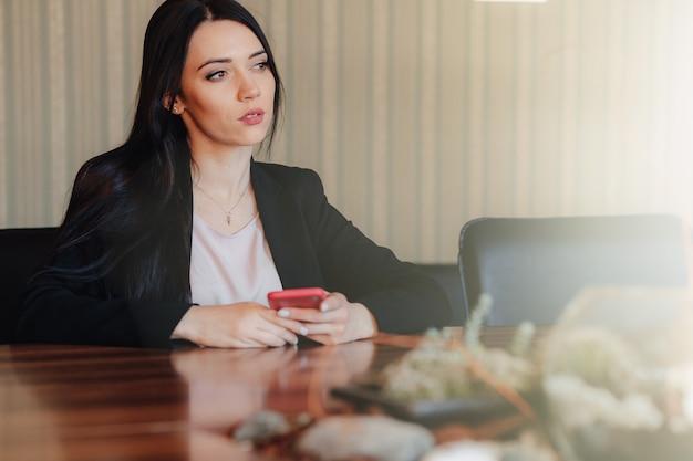Молодая привлекательная эмоциональная девушка в деловой стиль одежды, сидя за столом с телефоном в офисе или аудитории Бесплатные Фотографии