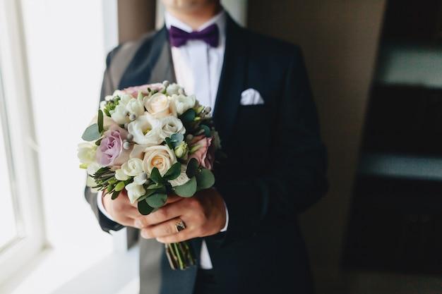 新郎は彼の手で結婚式のブーケを保持しています Premium写真