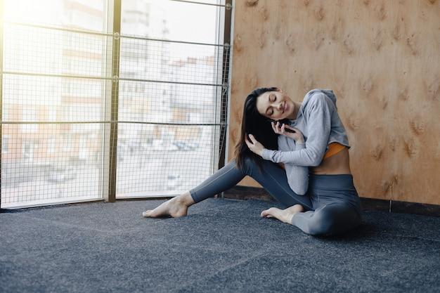 木製の壁の背景に窓の近くの床に座っている若い魅力的なフィットネス女の子。 Premium写真