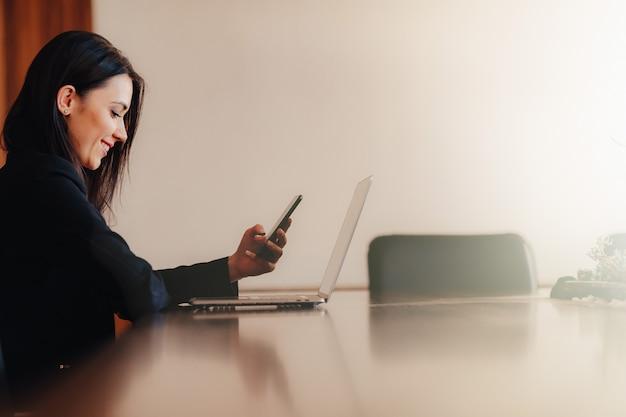 オフィスや観客の携帯電話で机に座ってビジネススタイルの服の若い魅力的な感情的な女の子 Premium写真