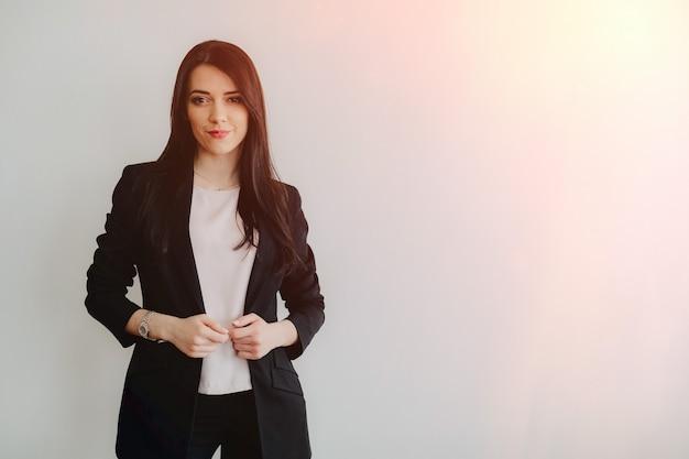 オフィスや観客の真っ白な背景にビジネススタイルの服の魅力的な感情的な少女 Premium写真