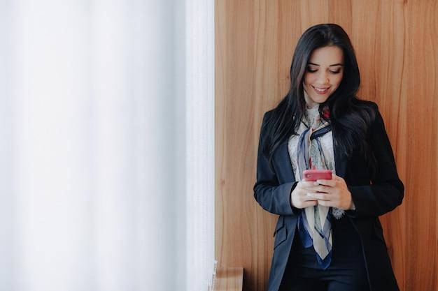 近代的なオフィスや講堂で電話でウィンドウでビジネススタイルの服の感情的な魅力的な少女 Premium写真