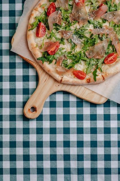 Неаполитанская пицца с салями, рукколой, помидорами посыпать сыром на деревянной доске на скатерть в клетке с местом для текста Бесплатные Фотографии