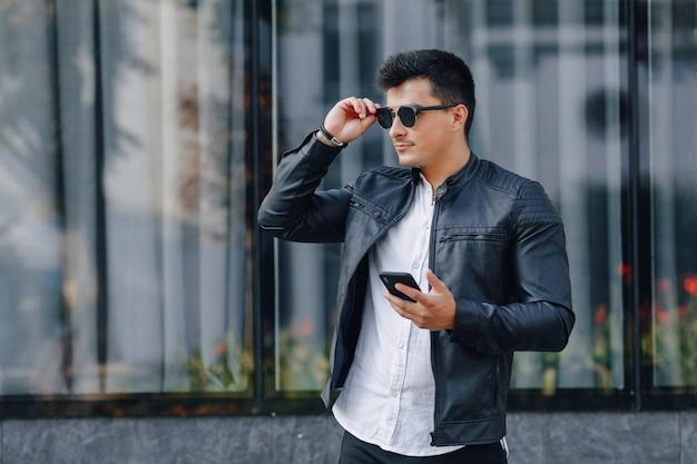 ガラス表面に電話で黒い革のジャケットでメガネの若いスタイリッシュな男 無料写真