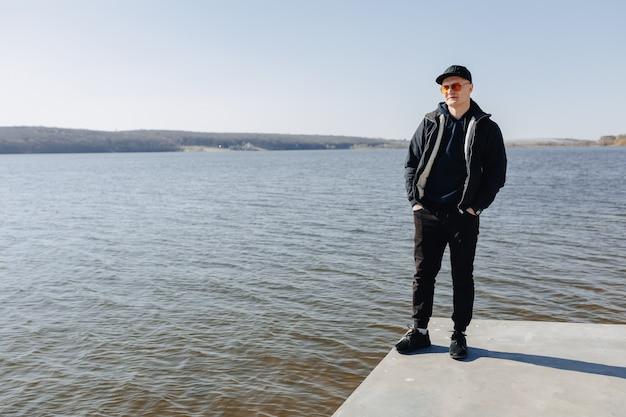 Стильный мальчик в оранжевых очках, куртке и кепке, прогулка по озеру весной или осенью Бесплатные Фотографии