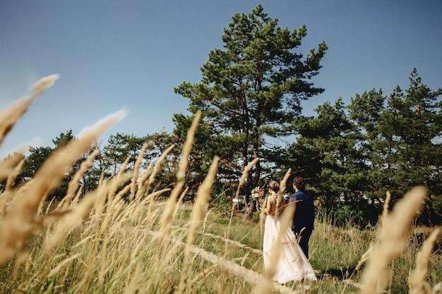 花嫁はブラシを通して森の中を歩きます Premium写真