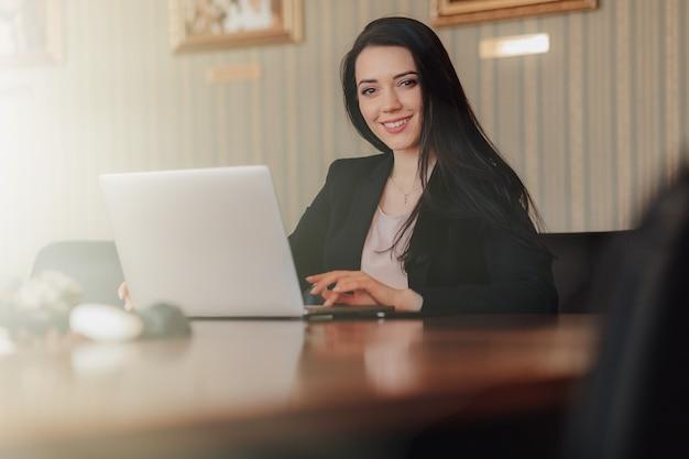 Молодая привлекательная эмоциональная девушка в деловом стиле одежды, сидя за столом на ноутбуке и телефон в офисе или аудитории Бесплатные Фотографии