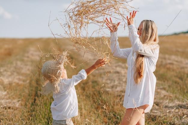 Белокурый мальчик играя с мамой с белыми волосами с сеном в поле. лето, солнечная погода, сельское хозяйство. счастливое детство Premium Фотографии