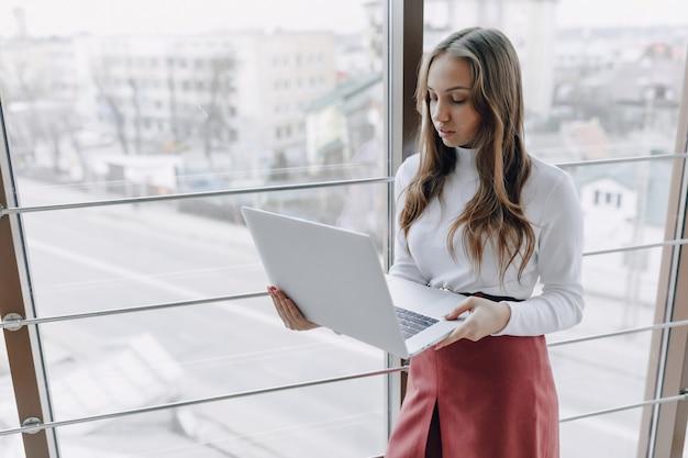 Хорошенькая молодая девушка с ноутбуком у окна в офисе с большими окнами. концепция удаленной работы. фрилансер работает один. Premium Фотографии