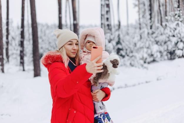 Мама держит ребенка на руках и делает селфи в снежной местности Premium Фотографии