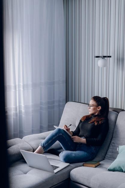 自宅のラップトップでソファで働く魅力的な少女。家にいる間の快適さと居心地の良さ。ホームオフィスと在宅勤務。リモートのオンライン雇用。 無料写真