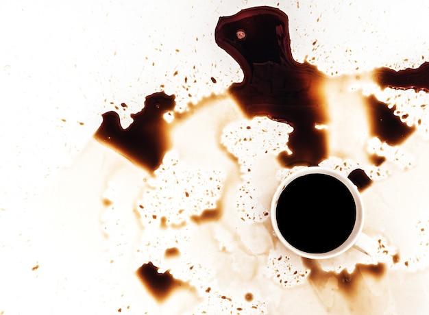 一杯のコーヒーが白い背景、上面図にこぼれた。グランジ広告デザイン、コピースペース Premium写真