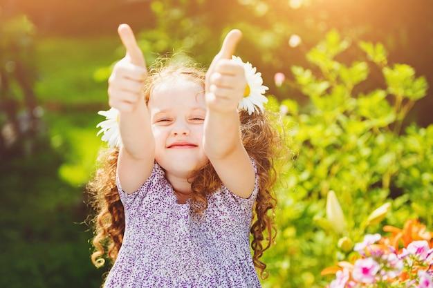 親指を現して、彼女の毛でデイジーと笑っている女の子。 Premium写真