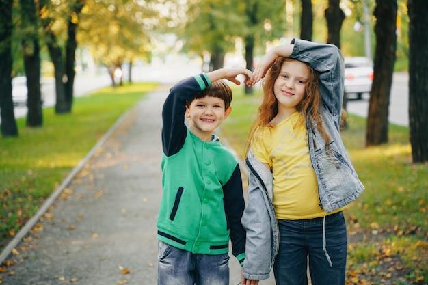 秋の公園で手を繋いでいる子供たち。 Premium写真