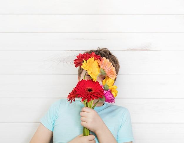 Милый мальчик с букетом цветов герберы. день матери, весна, пасха концепции. Premium Фотографии