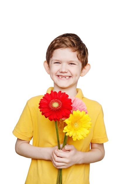 Смеющийся мальчик с букетом цветов герберы. Premium Фотографии