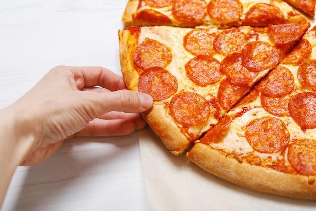 ピザのスライスを持っている人の手。 Premium写真