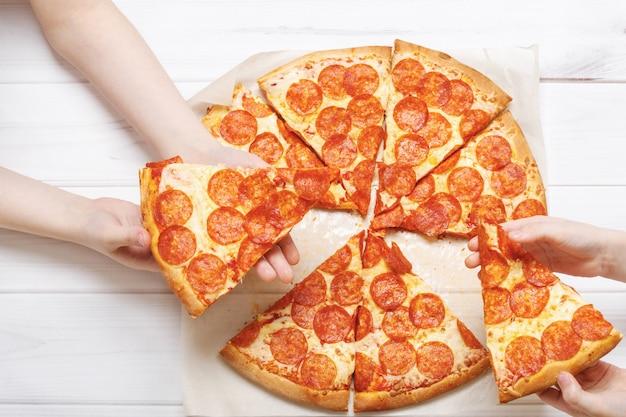 ピザのスライスを保持している子供たち。 Premium写真