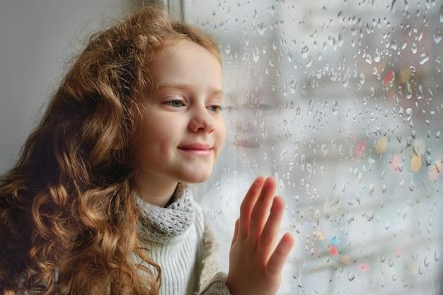 Счастливый ребенок, глядя в окно с мокрой стеклянной осенью плохой погоды. Premium Фотографии