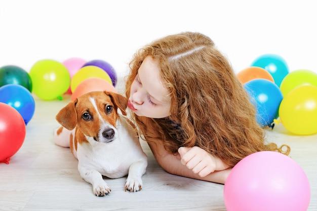 誕生日パーティーで彼女のジャックラッセルテリアとキスの女の子。 Premium写真
