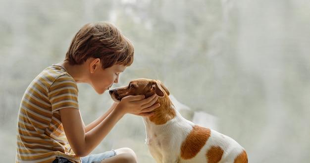子供が窓の上の鼻に犬をキスします。 Premium写真