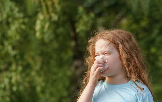 Больная маленькая девочка чихает в носовой платок на улице. Premium Фотографии