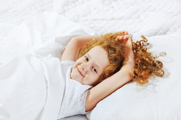 Сладкая девочка спит в постели. Premium Фотографии