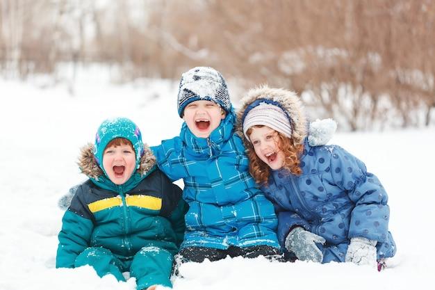 Смеются дети, сидящие на снегу. Premium Фотографии