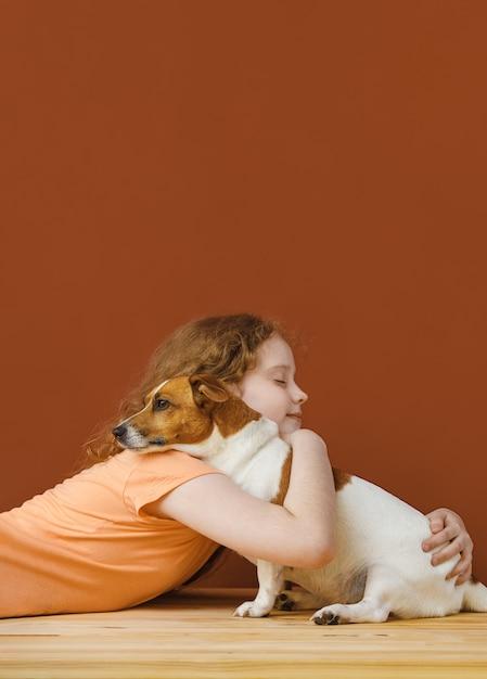 彼女の友人の犬を抱きしめる巻き毛の少女。 Premium写真