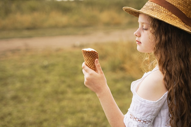麦わら帽子の巻き毛の少女は、夏に村でアイスクリームを食べる Premium写真