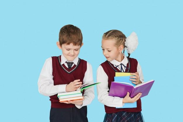 水色の壁に本を持つ子ども。 Premium写真