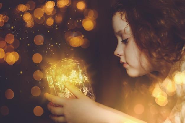 魔法のクリスマスランプを探している少女。 Premium写真