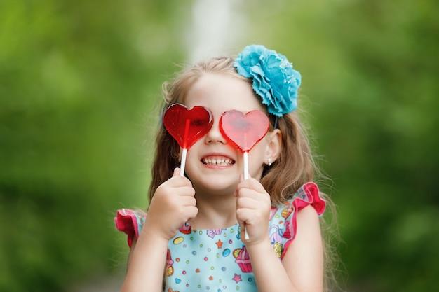 ハート型のロリポップで面白い女の子は、彼の白い歯を示しています。 Premium写真