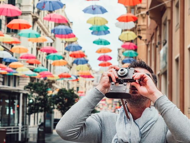 Красивый человек с камерой года сбора винограда на дождливый день. Premium Фотографии