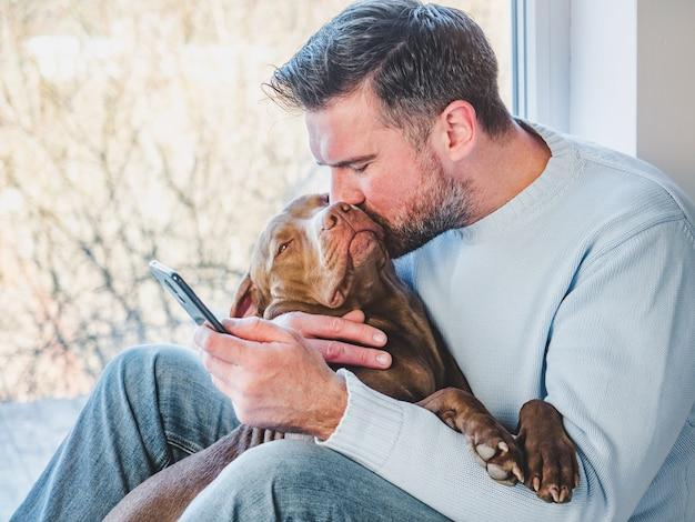Красивый мужчина и очаровательный щенок. крупный план Premium Фотографии