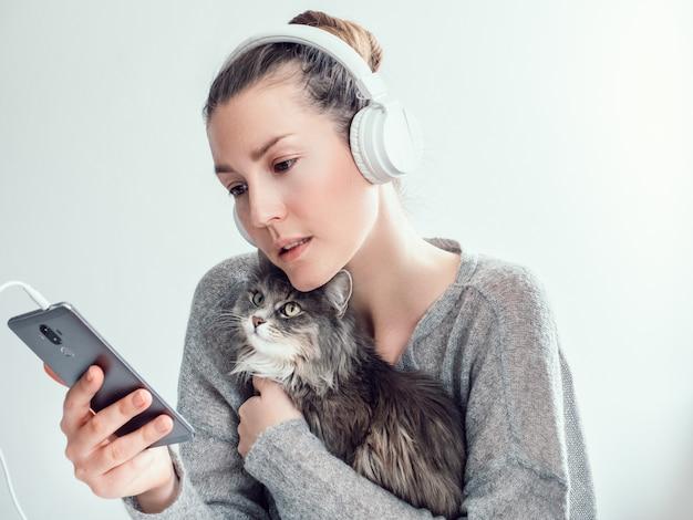 ヘッドフォンと彼女の子猫とスタイリッシュな女性 Premium写真