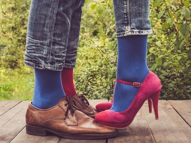 Ноги молодой пары в стильной обуви и ярких носках Premium Фотографии
