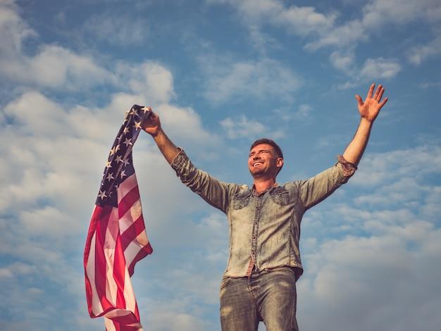 アメリカの国旗を保持しているハンサムな若い男 Premium写真