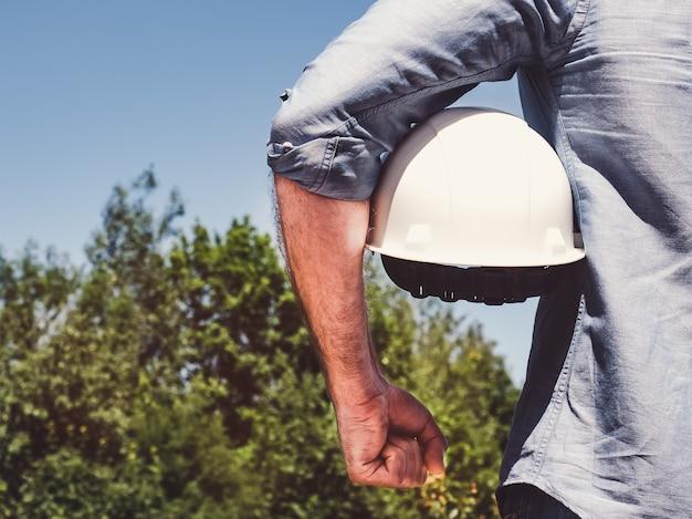 Инженер, держащий белый шлем в парке Premium Фотографии