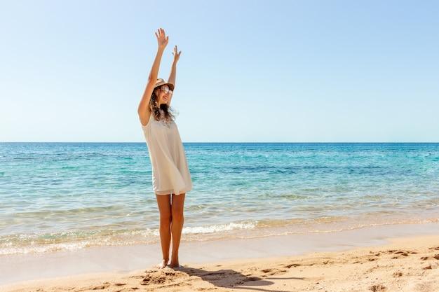 夏の自由を楽しんでいるビーチでリラックスした女性。ビーチでの幸せな女の子 Premium写真