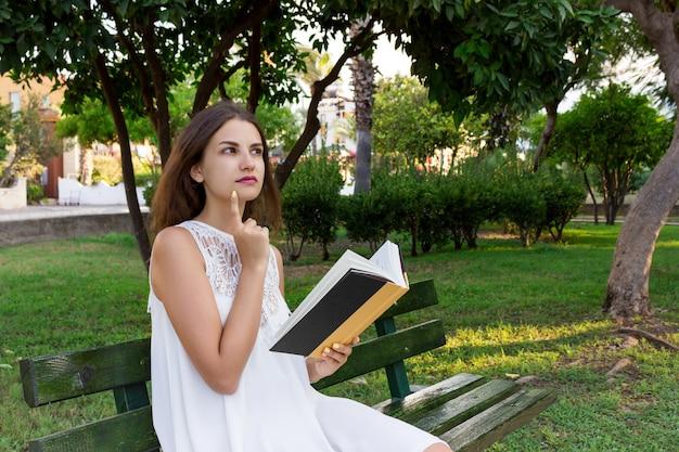 若い女性は公園のベンチに座っていると彼女が読んだことについて考えています Premium写真