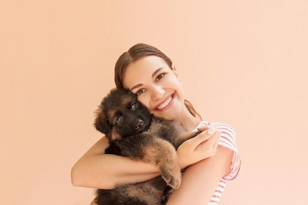 若い女性は小さなかわいい子犬を抱いて楽しんでいます Premium写真