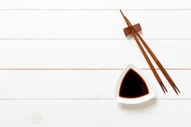 白い木製のテーブルの上の箸と醤油 Premium写真