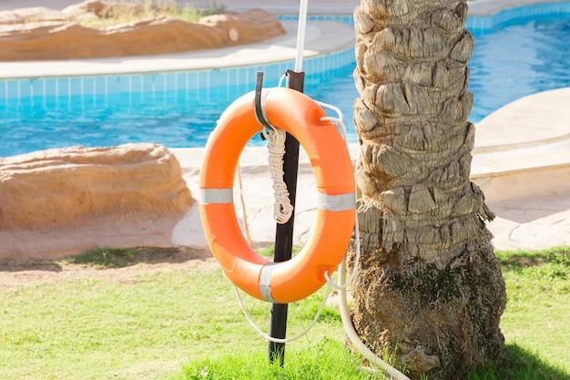 ホテルで休暇中にプールの近くのフェンスにぶら下がっているオレンジ色の緊急救命浮輪 Premium写真