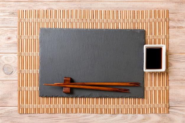 木の寿司と醤油の箸で空の長方形ブラックスレートプレート Premium写真